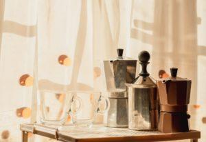 Moka pot and cups on table